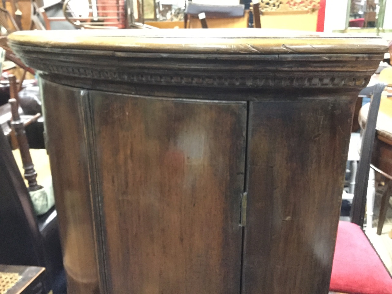 Lot 52 - A barrel fronted nineteenth century mahogany corner cabinet with moulded dentil cornice above two