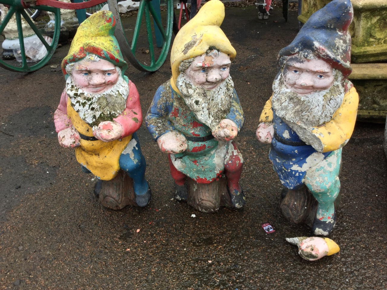 Lot 21 - A set of three colourful garden gnomes, the bearded composition stone figures seated on logs. (23in)