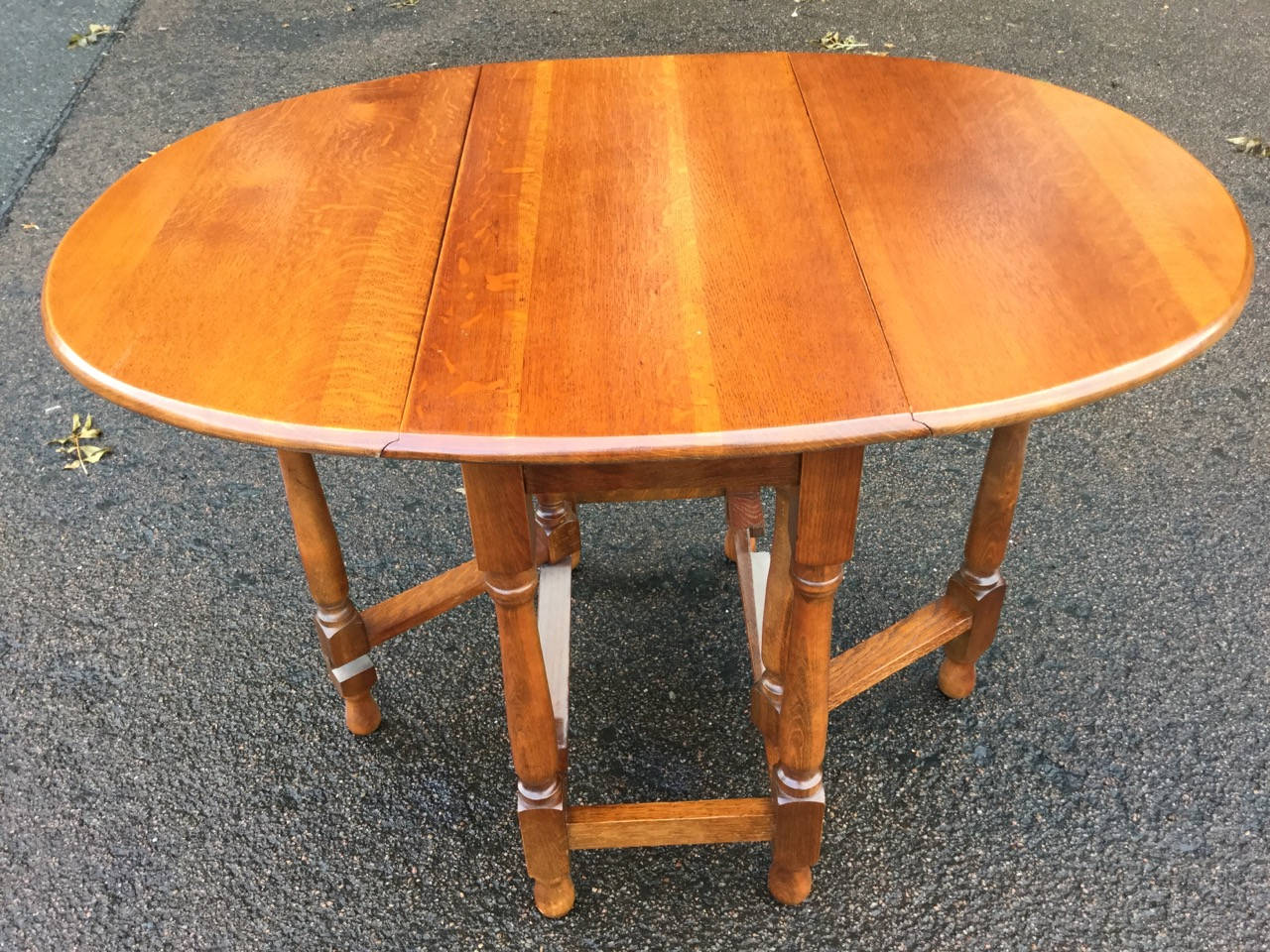 Lot 18 - An oval oak gateleg dining table, the moulded top with two drop-leaves raised on baluster turned