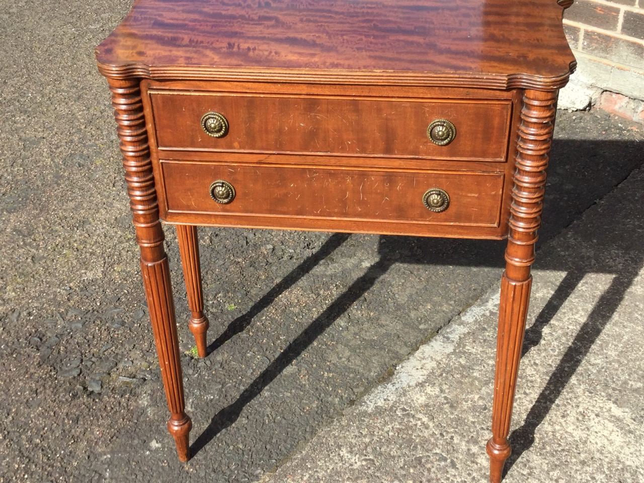 Lot 40 - A mahogany side cabinet, the shaped top with ribbed edge above two cockbeaded drawers framed by