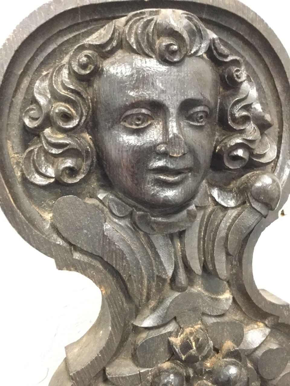 Lot 60 - A Victorian carved oak panel, the waisted piece with eighteenth century style head above a fruit