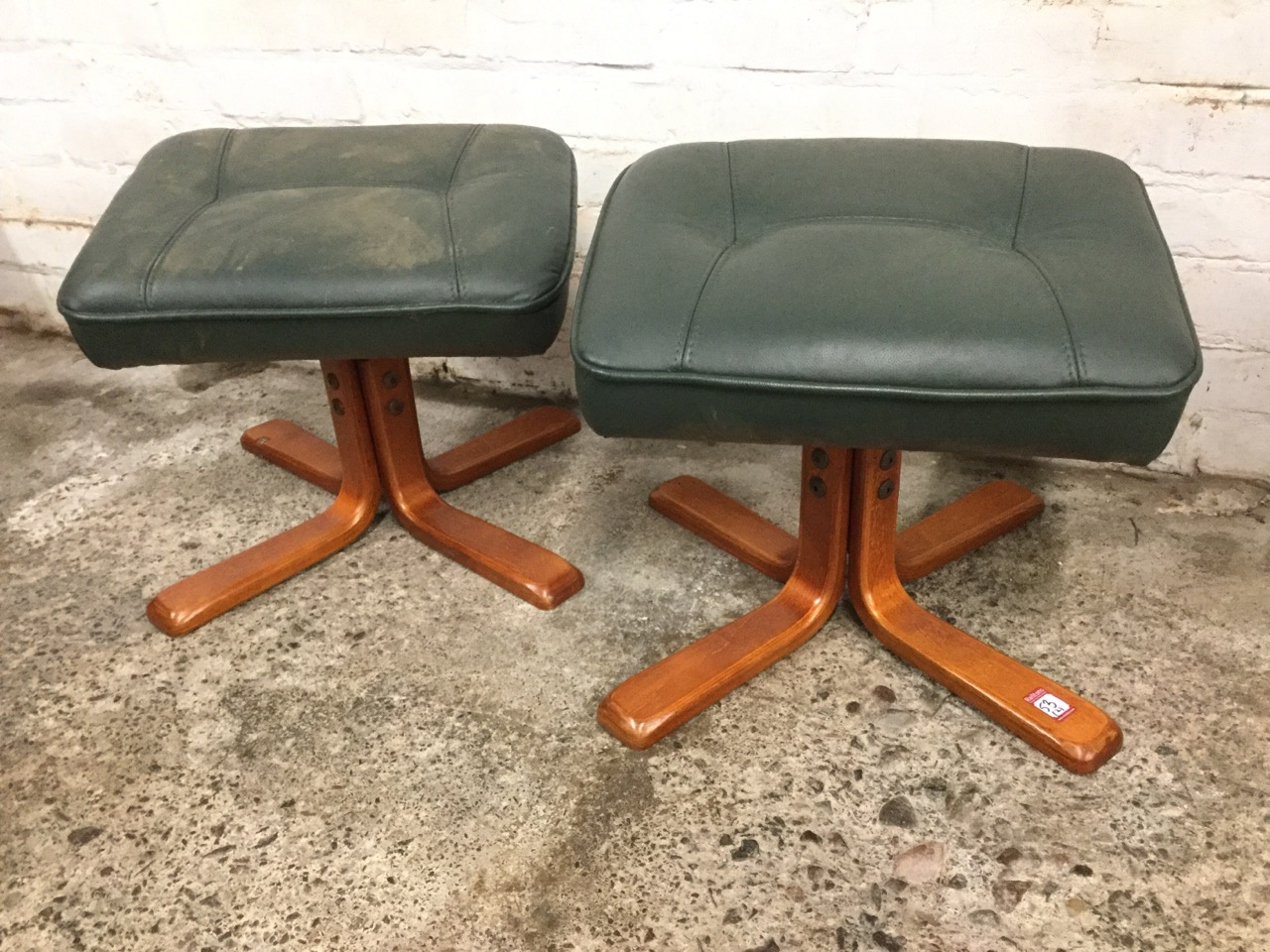Lot 53 - A pair of contemporary rectangular leather upholstered stools, with angled panel stitched tops on