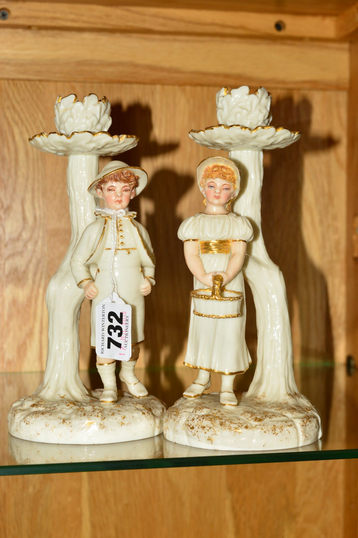 Lot 732 - A PAIR OF ROYAL WORCESTER KATE GREENWAY STYLE FIGURAL CANDLESTICKS, modelled by James Hadley,