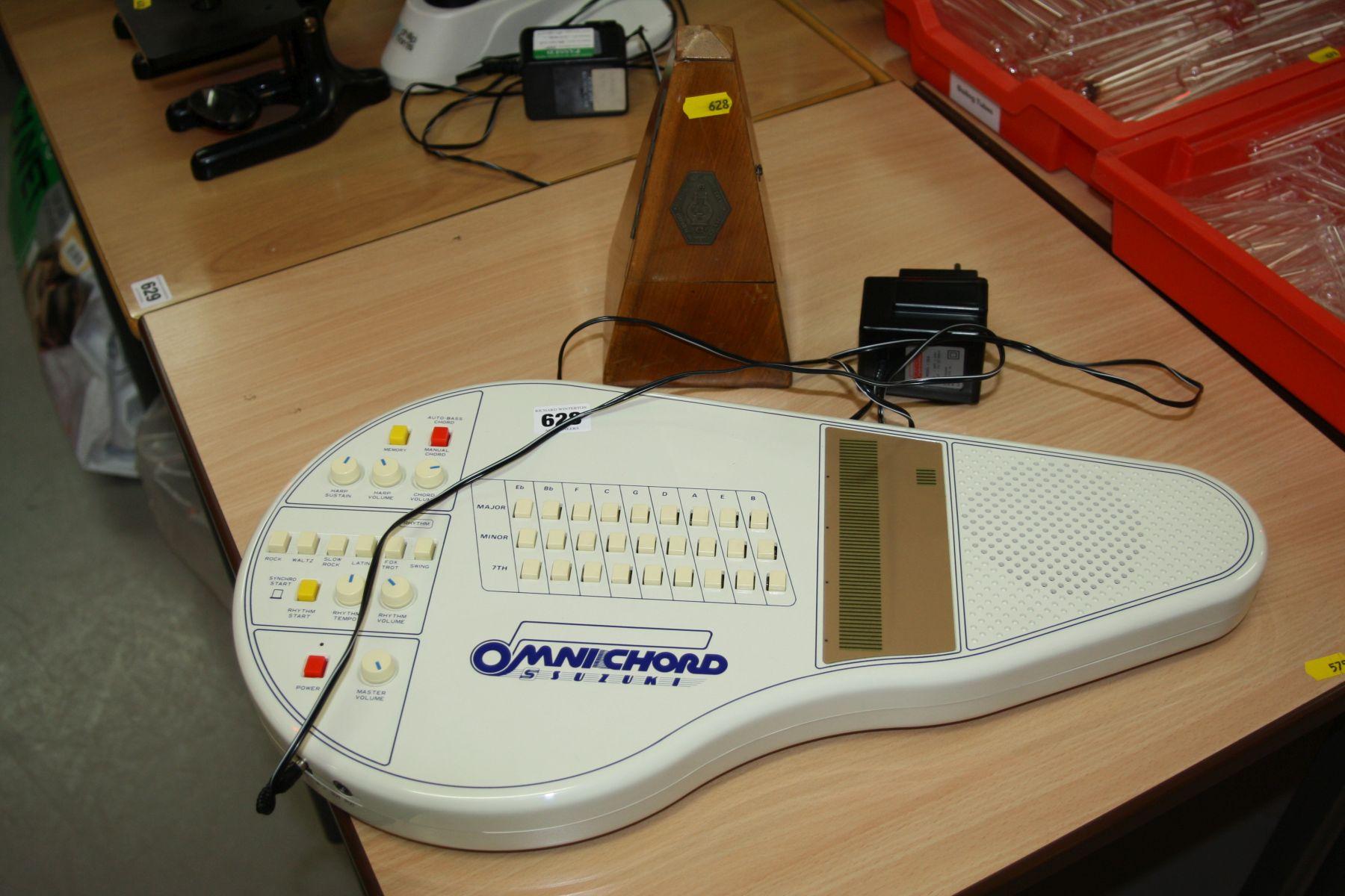 Lot 628 - A SUZUKI ELECTRONIC OMNI CHORD, with PSU and a clockwork metronome (no winder)