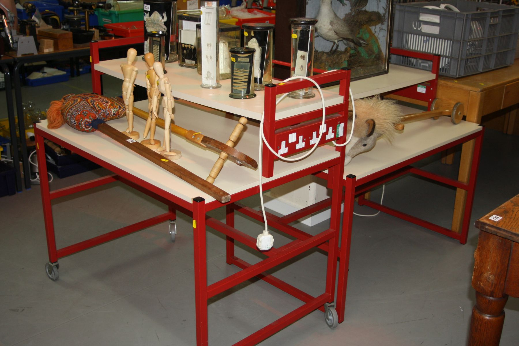 Lot 766 - TWO LAMINATE AND METAL TWO TIER TROLLEY DESKS, fitted with electric sockets to one end, width