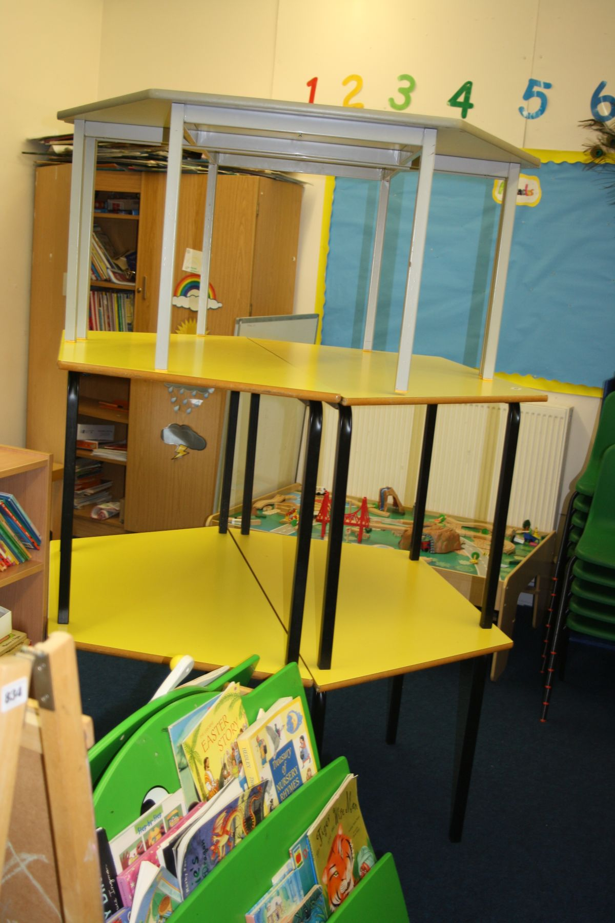 Lot 833 - FOUR YELLOW AND BLACK CHILDS TABLES, with angled ends and a matching rectangular table,