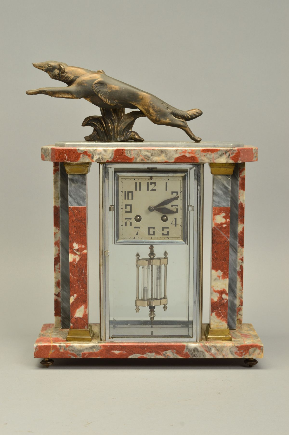 Lot 272 - A FRENCH ART DECO MARBLE MANTEL CLOCK, surmounted by a spelter dog on a grey and orange veined