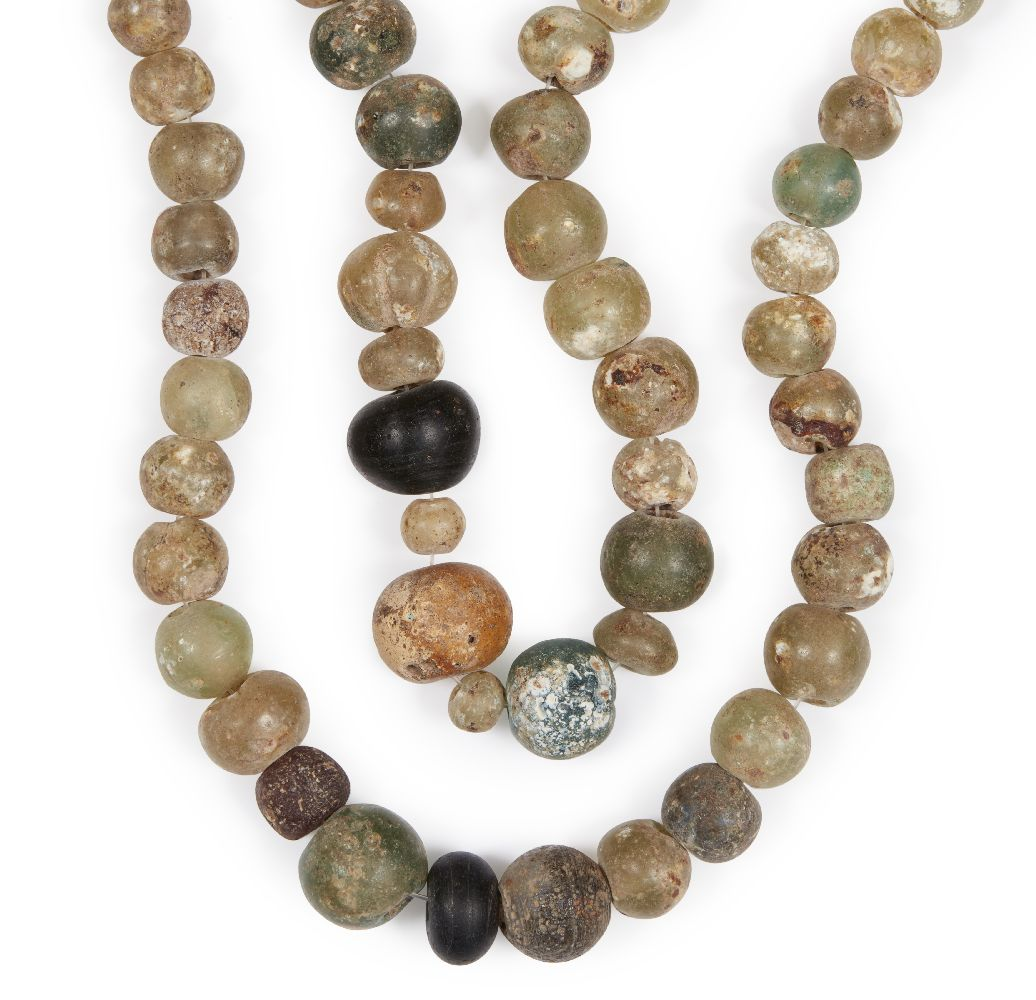 Lot 66 - Two Roman glass bead necklaces, 2nd-8th century, comprised of round clear glass beads, one with an