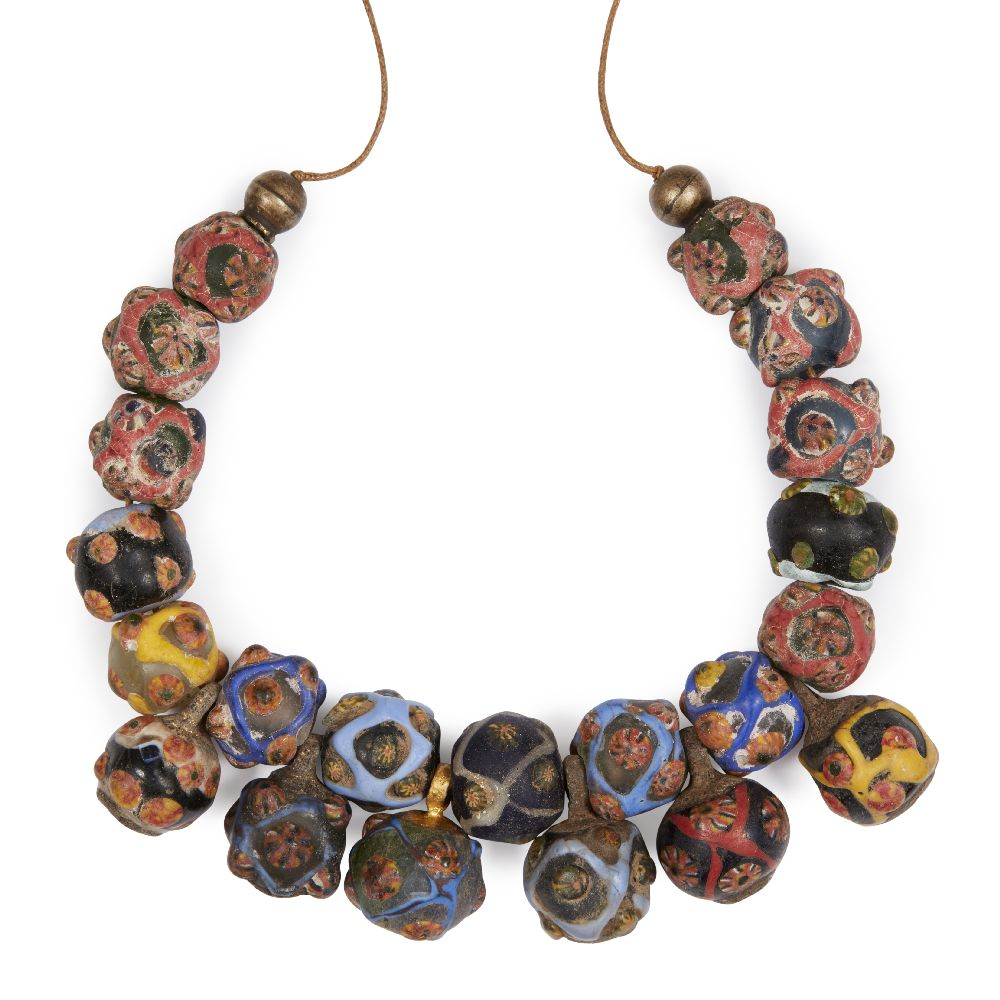 Lot 128 - A necklace of mosaic glass beads with cane eyes, Syria or Iran, 8th-11th century, comprising 15