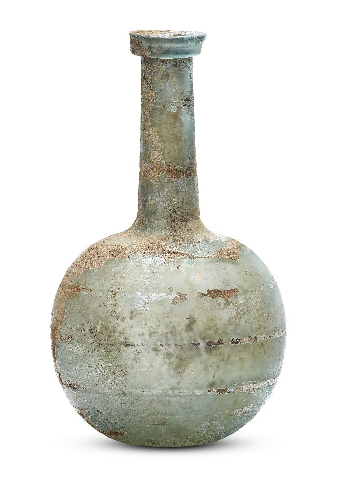 Lot 81 - A Roman bluish-green glass bottle, 1st-2nd century A.D., with a folded collar rim on a long