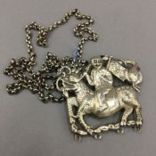 A Chinese white metal pendant necklace formed as a figure riding a dragon