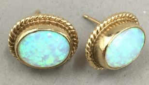 A pair of unmarked gold and opal earrings