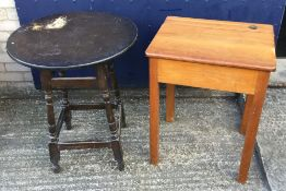 A small wooden school desk with lift up-lid and a mid 20th century round wooden pub table