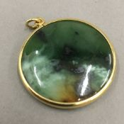 An 18 ct gold framed greenstone pendant (11 grammes total weight)