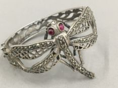 A marcasite set unmarked silver bracelet decorated with a dragonfly