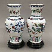 A pair of Franklin Mint Chinese porcelain vases on wooden stands