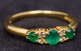 An 18 ct gold diamond and emerald ring The three emeralds interspersed with small diamonds.