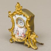 A late 19th century Continental enamel decorated gilt bronze desk clock The white enamelled dial