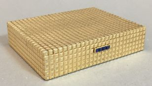 A Cartier 14K gold box Of hinged rectangular form, with blue cabochon set clasp. 7.5 cm wide.