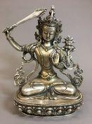 A Sino-Tibetan white metal deity Typically worked seated on a lotus plinth. 21.5 cm high.