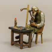 A cold painted bronze figure Modelled as a cobbler at work. 5 cm wide.