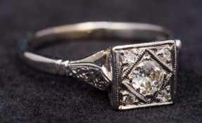 An Art Deco 18 ct white gold and platinum diamond ring The centrally set stone flanked by four