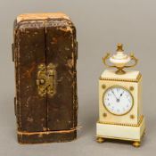 A 19th century ivory cased miniature desk clock Of stepped rectangular form surmounted with an urn,