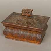 An early 19th century carved wooden box and cover The domed removable lid with flowering urn finial,