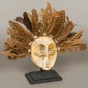 A Lega Tribe of the Democratic Republic of Congo ivory mask Decorated with an unusual feather and