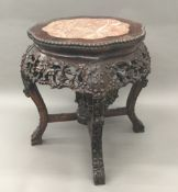 A Chinese carved rosewood marble inset urn stand The shaped top above a profusely carved apron and