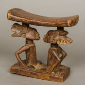 An African tribal wooden headrest The stand carved as two kneeling figures. 17.5 cm high.