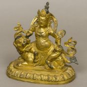 A Chinese gilt bronze figure of a deity Modelled seated atop a dog-of-fo. 18 cm high.