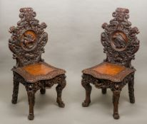 A pair of Victorian profusely carved oak hall chairs Each scroll carved top rail above a carved