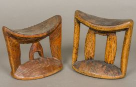 Two African tribal carved wooden headrests Each of typical curved form with end and central carved