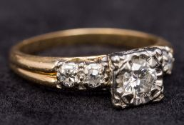A 14 ct gold and diamond ring With square set central stone above the diamond set shoulders.