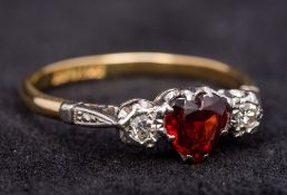 An 18 ct gold diamond and garnet ring The central heart shaped garnet flanked by two diamonds.
