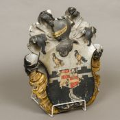 A 19th century painted carved marble heraldic crest Painted with three birds,