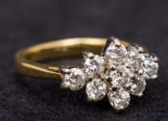 An 18 ct gold diamond cluster ring Set with nine small diamonds. 1.5 cm wide.