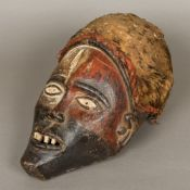 An African tribal carved wooden mask With traces of original paint pigment and mounted with an
