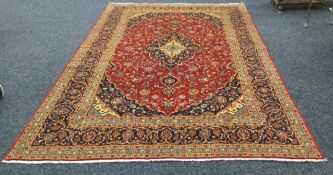 A Kashan wool carpet The wine red field with central medallion with pendant palmettes within