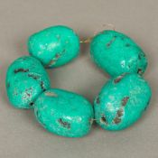 Five large turquoise beads Of natural rough form. The largest 5.5 cm long.