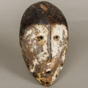 An African tribal carved wooden mask With traces of original lime pigment. 24 cm high.