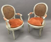 A pair of late 19th/early 20th century caned painted open armchairs Each shaped moulded caned oval