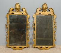 A pair of 18th century gilt framed wall glasses Each with broken swan-neck pediment centred with a