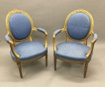 A pair of Louis XV style upholstered giltwood open armchairs Each tied wreath topped padded oval