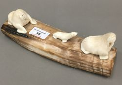 A carved whales tooth walrus family,