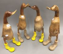 A set of four wooden ducks in boots