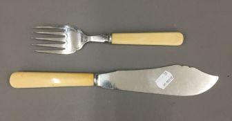 An engraved hallmarked silver fish slice and fork with ivory handles,