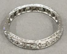 An unmarked white gold, possibly 18 ct, diamond eternity ring, hand engraved (2.
