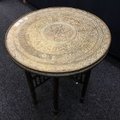 An Eastern brass topped folding table